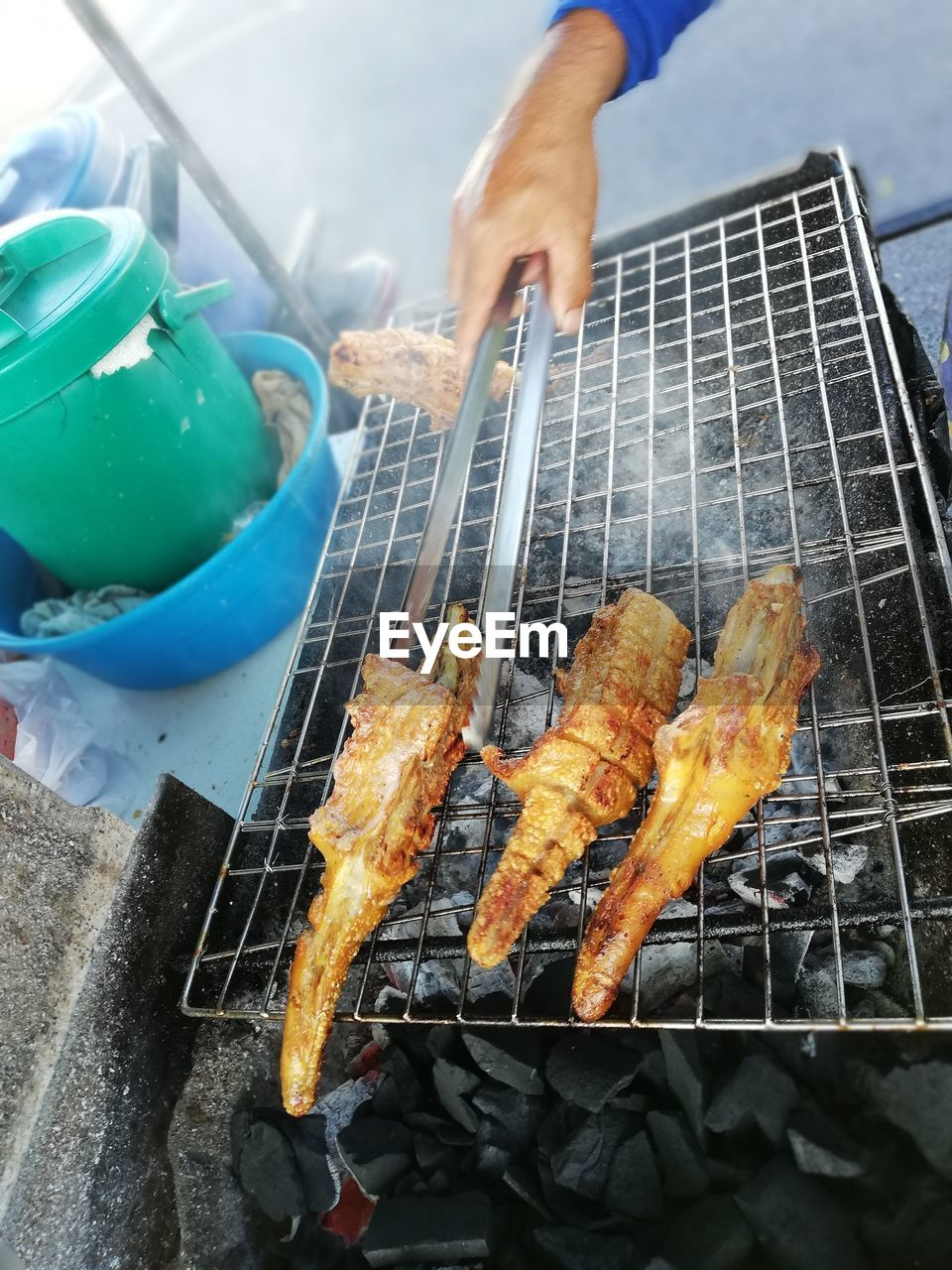 food, food and drink, preparation, one person, barbecue, real people, meat, holding, freshness, heat - temperature, human hand, barbecue grill, hand, unrecognizable person, preparing food, human body part, outdoors, day, high angle view, finger