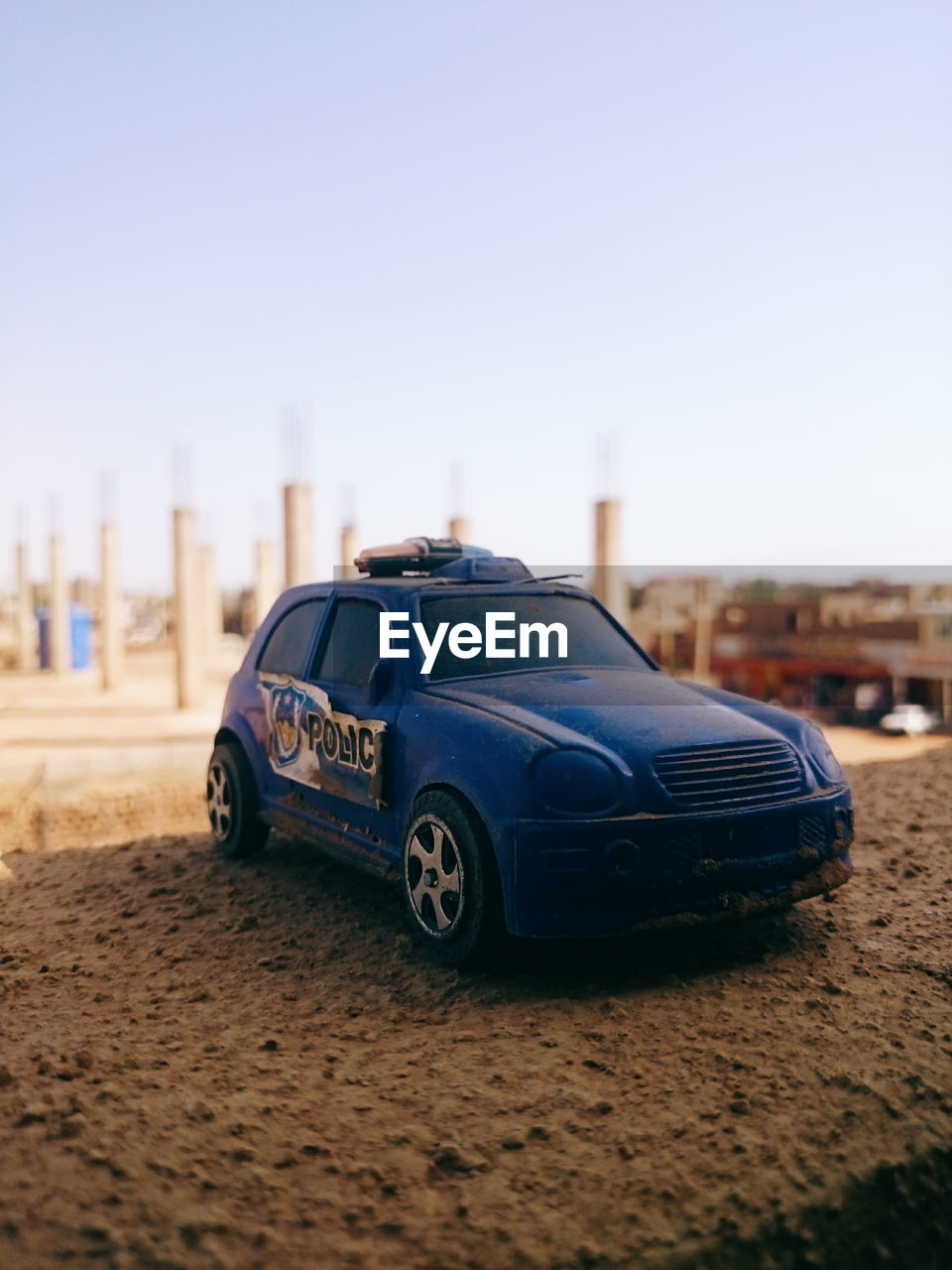 car, motor vehicle, transportation, mode of transportation, sky, built structure, architecture, city, copy space, land vehicle, nature, clear sky, day, building exterior, no people, selective focus, focus on foreground, land, sand, blue