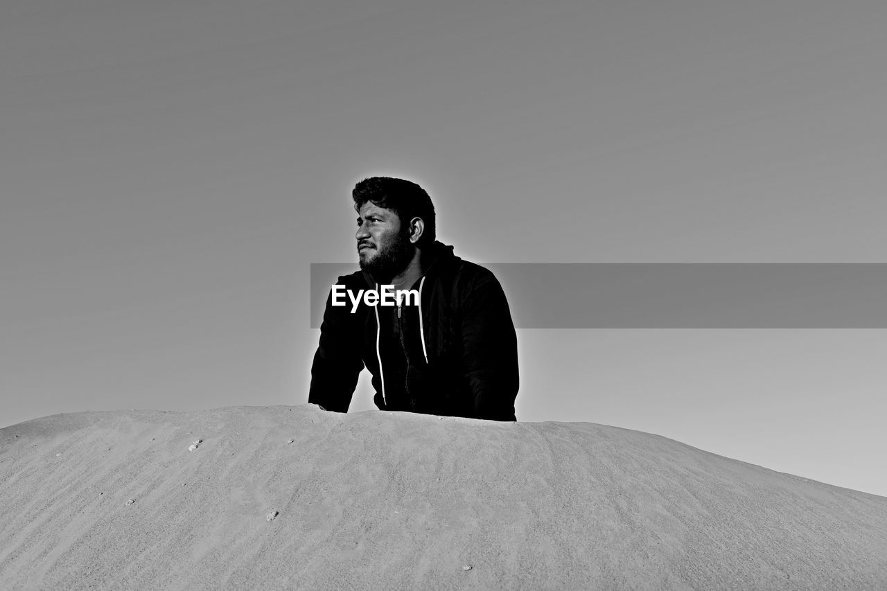 one person, real people, young men, copy space, lifestyles, sky, front view, looking away, young adult, clear sky, looking, sitting, men, leisure activity, nature, waist up, males, low angle view, contemplation