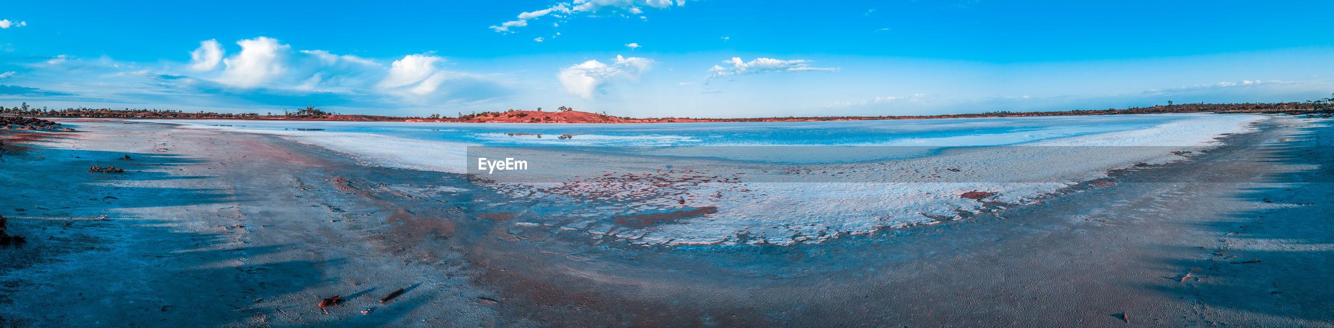 Panoramic shot of frozen lake against blue sky