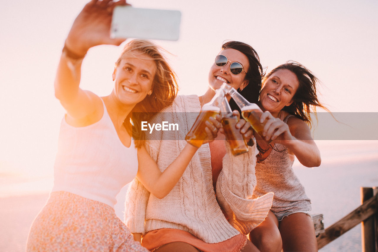 Smiling Friends With Alcoholic Drinks Taking Selfie At Beach Against Sky During Sunset