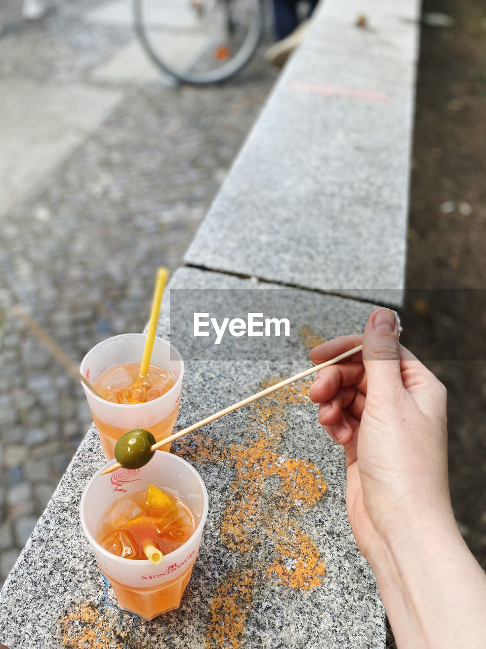 HIGH ANGLE VIEW OF PERSON HOLDING DRINK