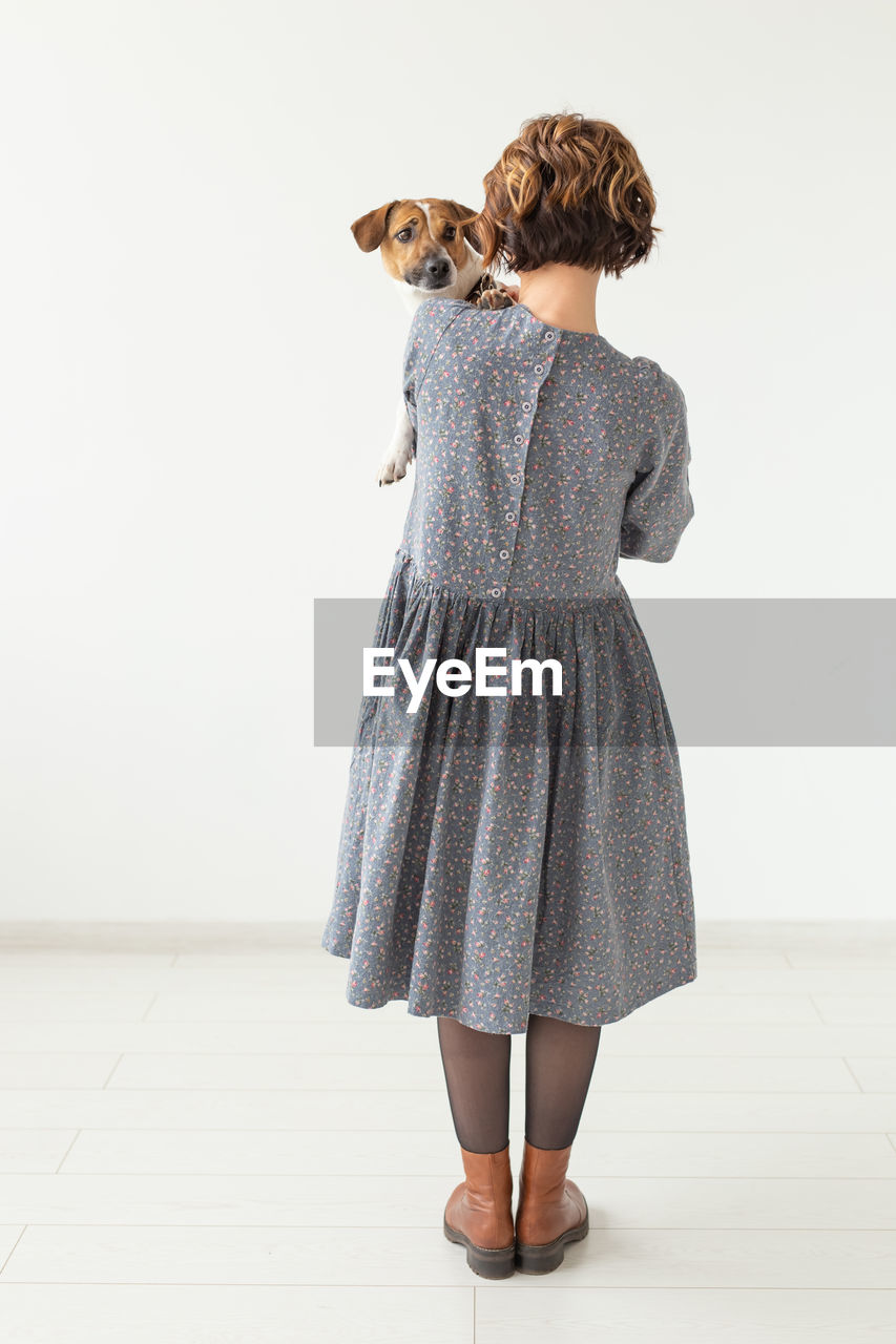 FULL LENGTH REAR VIEW OF WOMAN STANDING ON SMALL WALL
