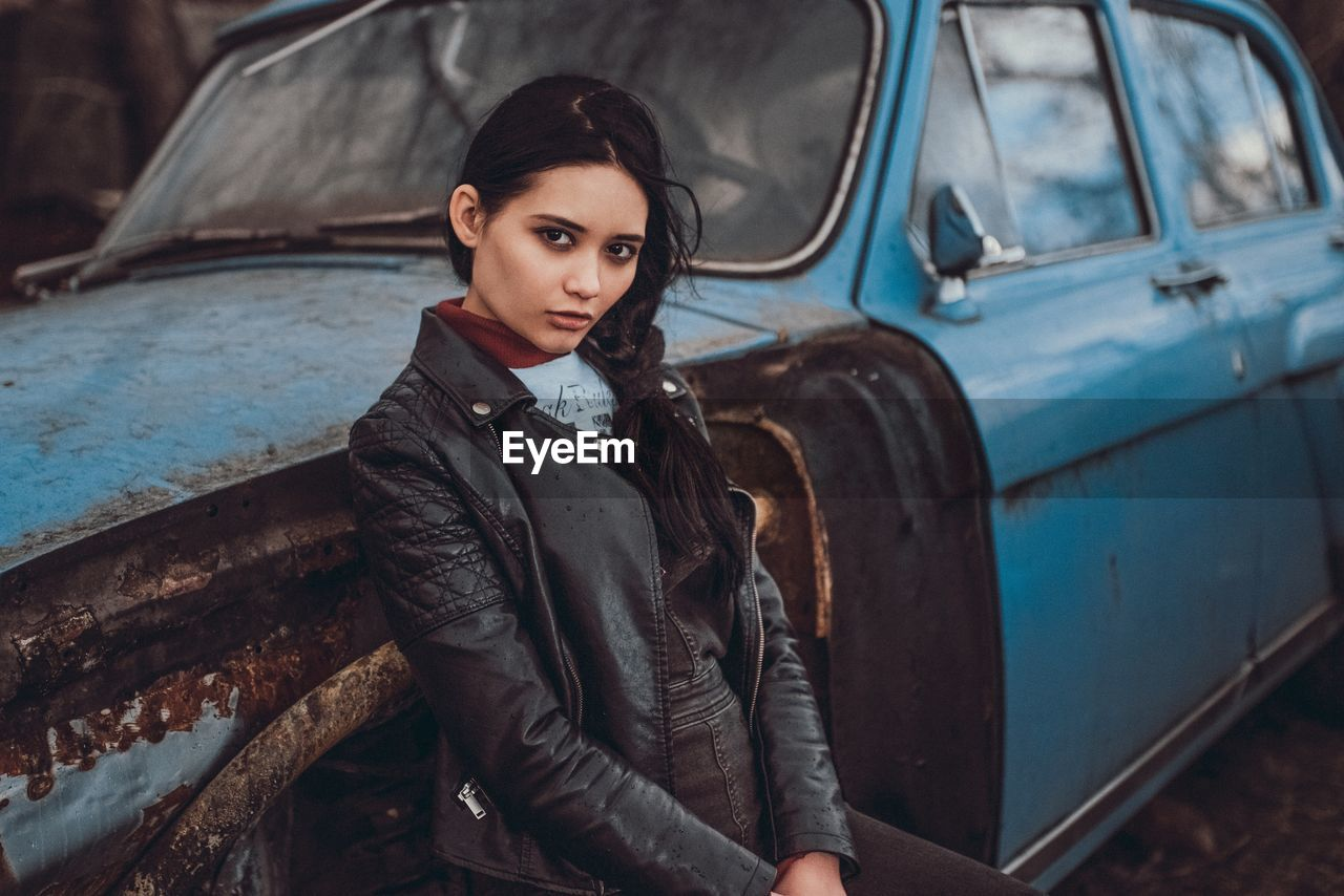 Portrait of young woman standing by abandoned car