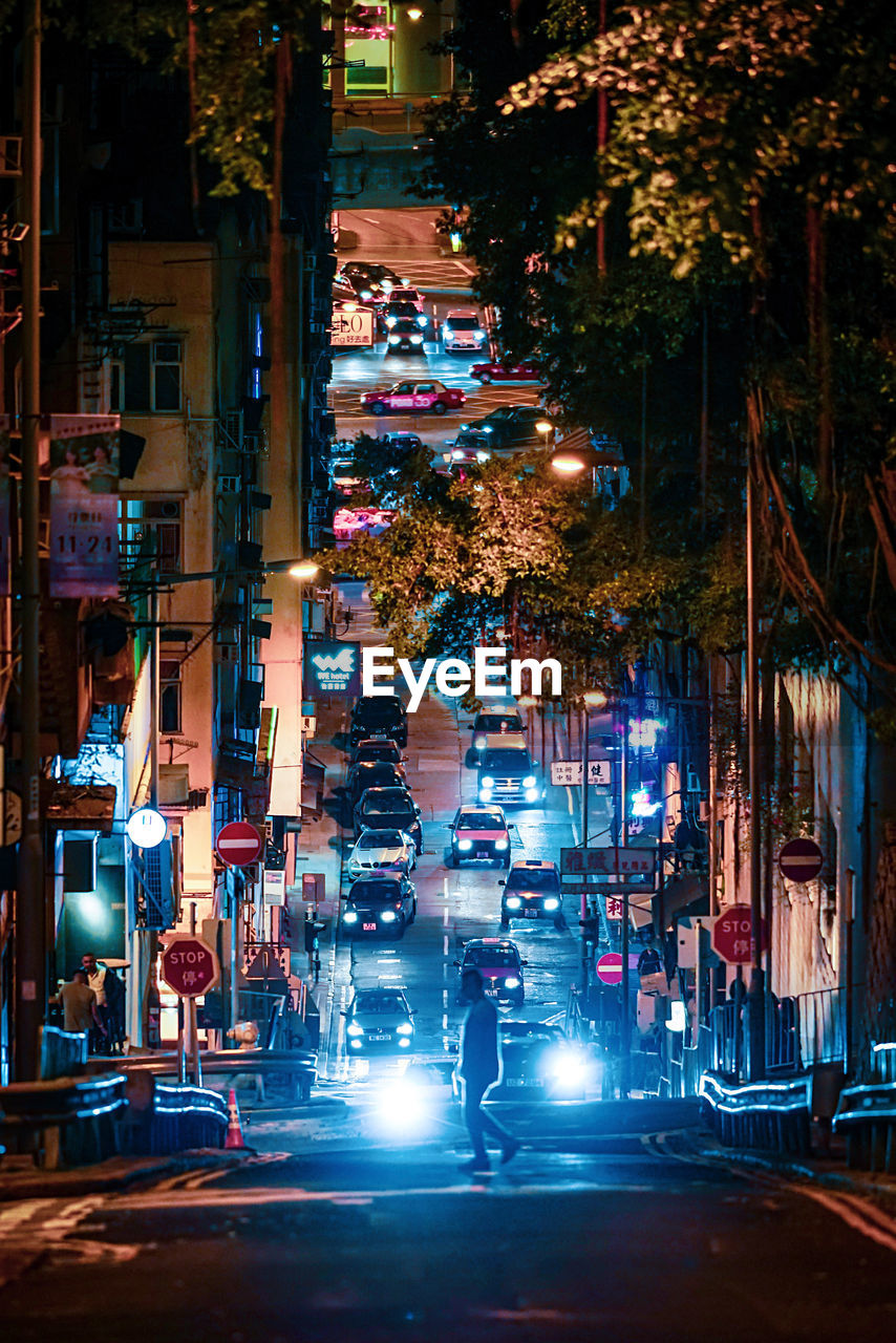 illuminated, city, night, street, architecture, building exterior, built structure, transportation, city life, mode of transportation, motor vehicle, land vehicle, car, city street, real people, incidental people, road, people, building, outdoors, nightlife