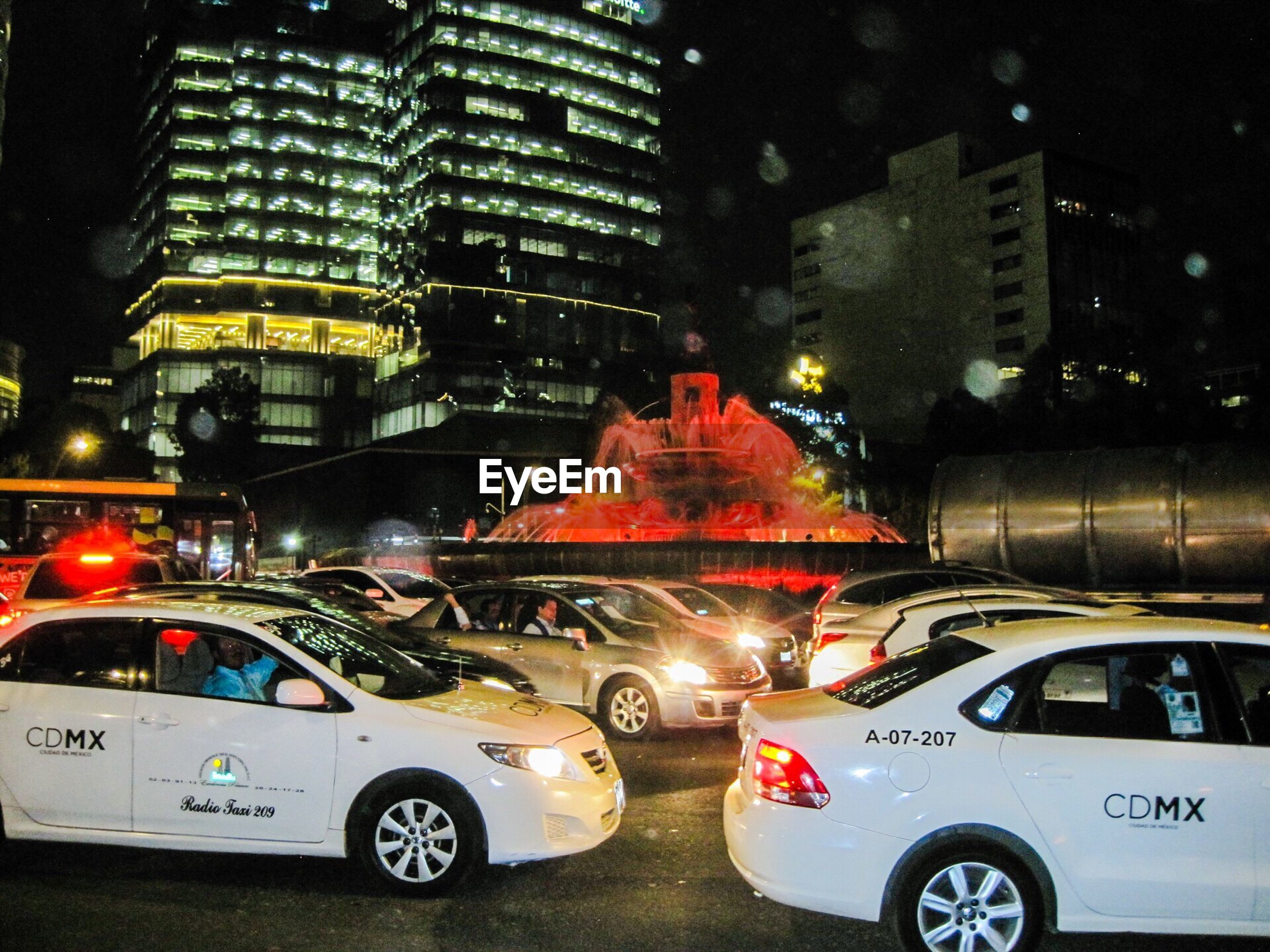 car, transportation, city, night, illuminated, taxi, mode of transport, land vehicle, traffic, city life, yellow taxi, building exterior, architecture, skyscraper, outdoors, no people, snowing, police car