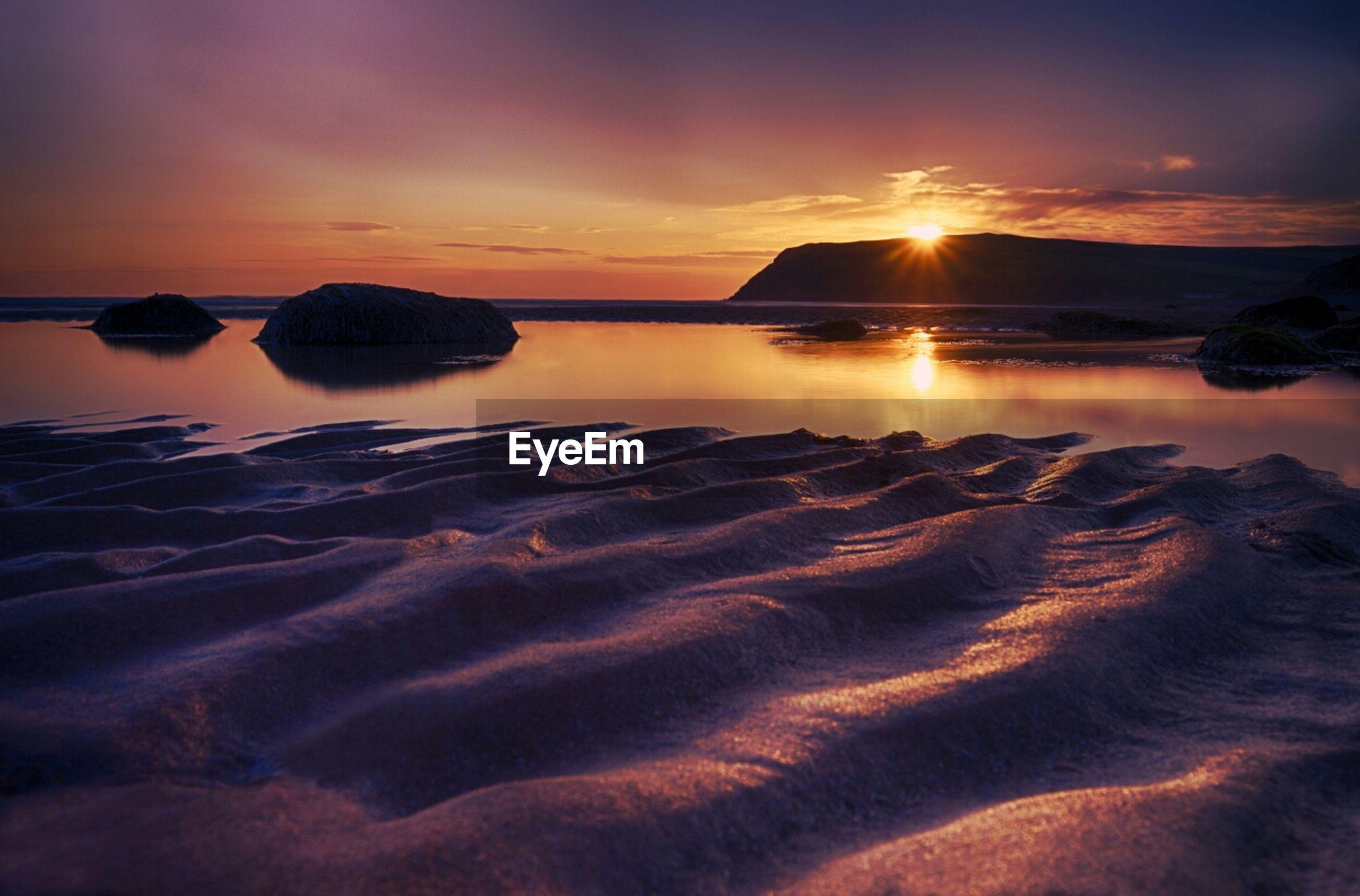 sunset, water, tranquil scene, scenics, tranquility, beauty in nature, sea, sky, beach, reflection, orange color, nature, idyllic, sun, shore, cloud - sky, sand, majestic, sunlight, mountain