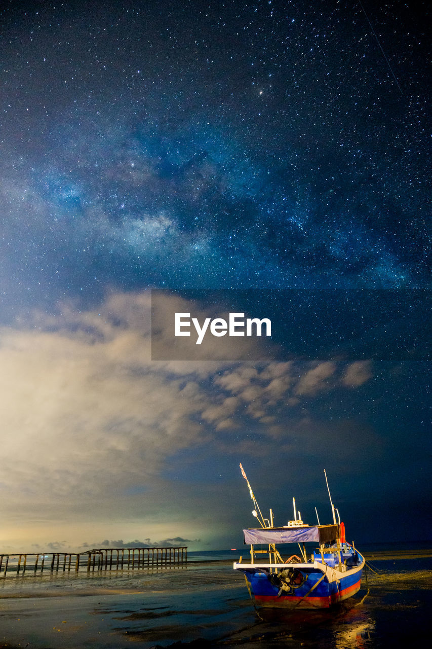 Boat Anchored At Sea With Clouds And Stars In Sky At Dusk