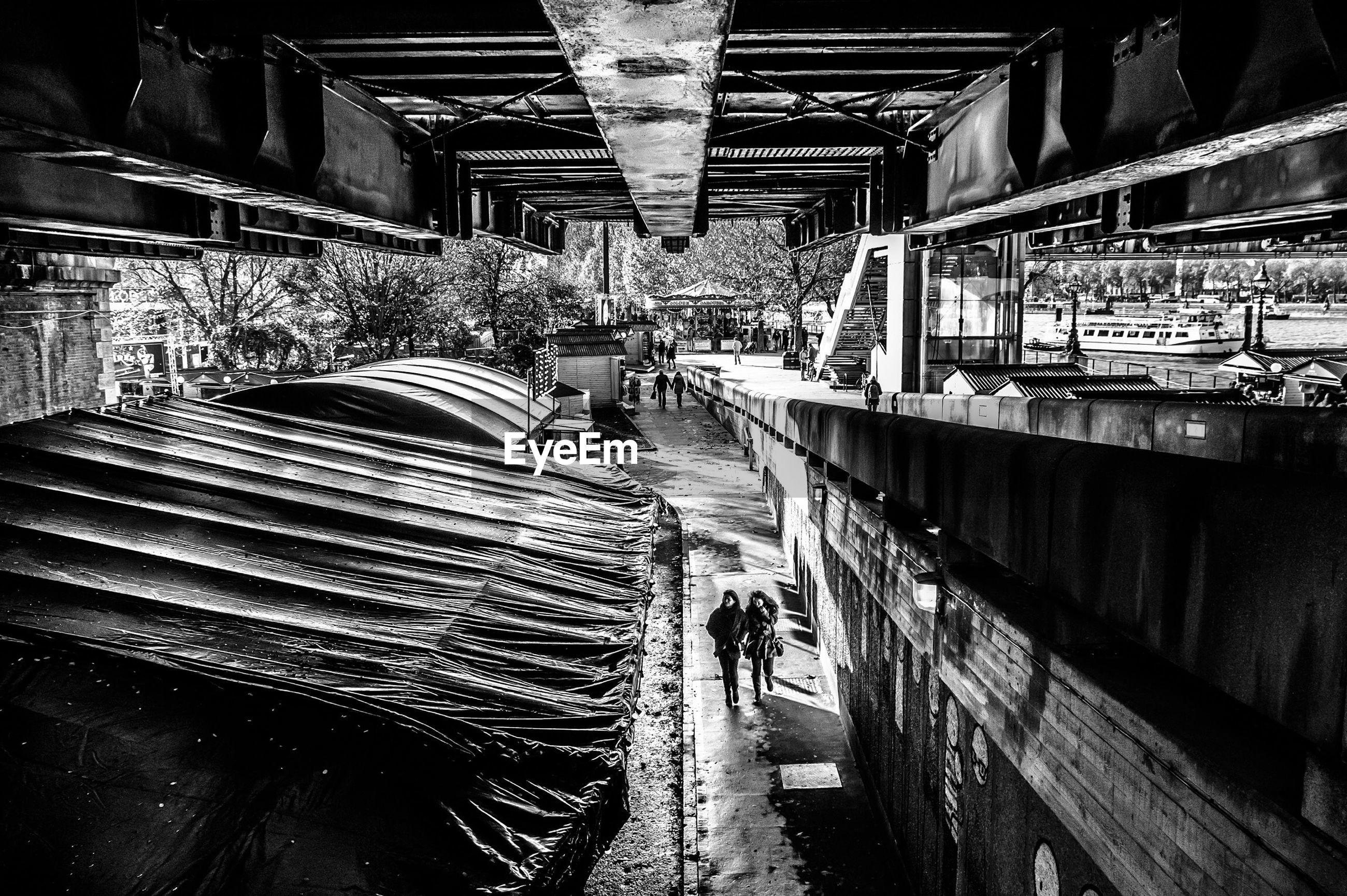 High angle view of women walking on street under bridge