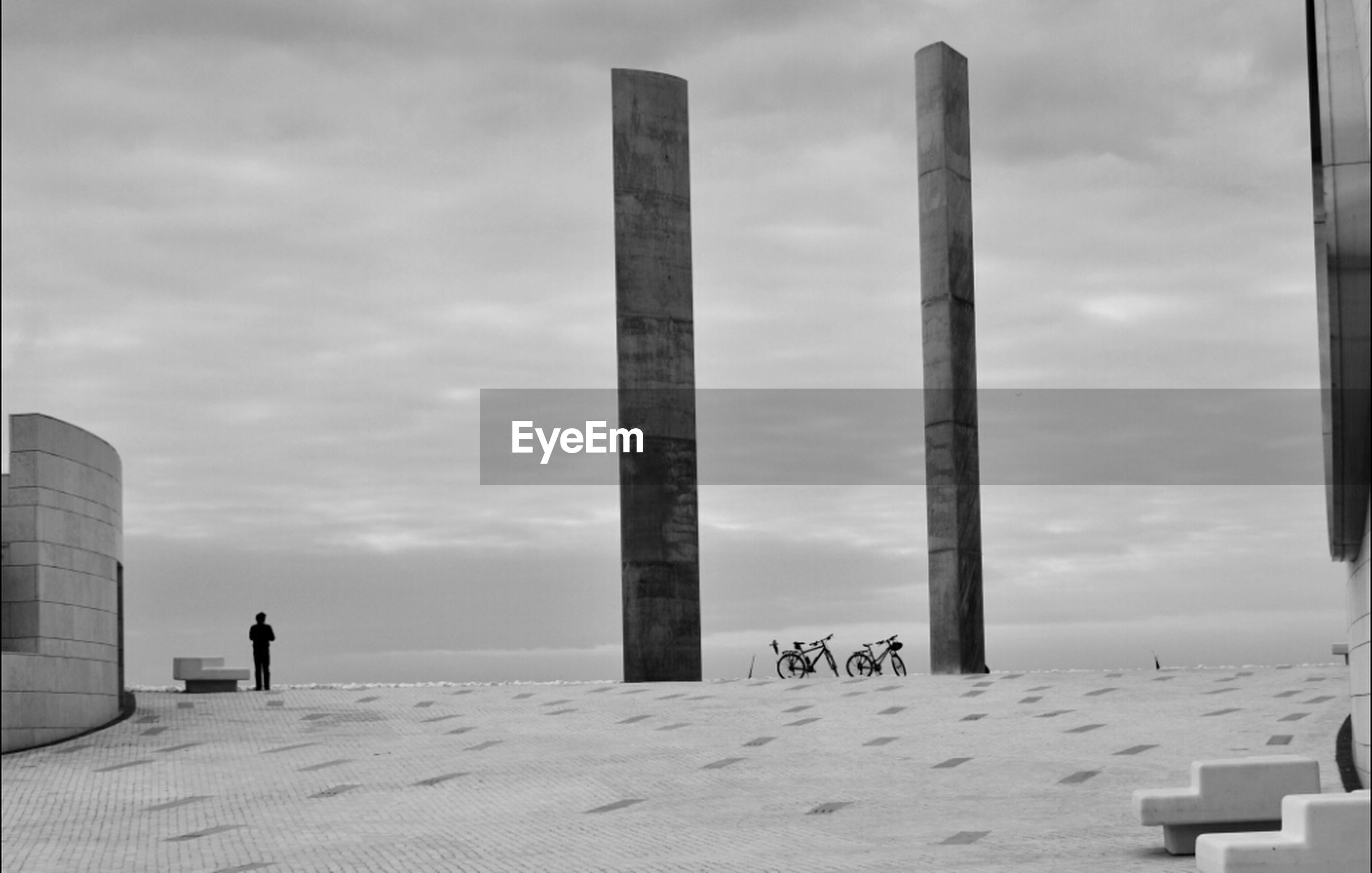 Low angle view of columns on beach against cloudy sky