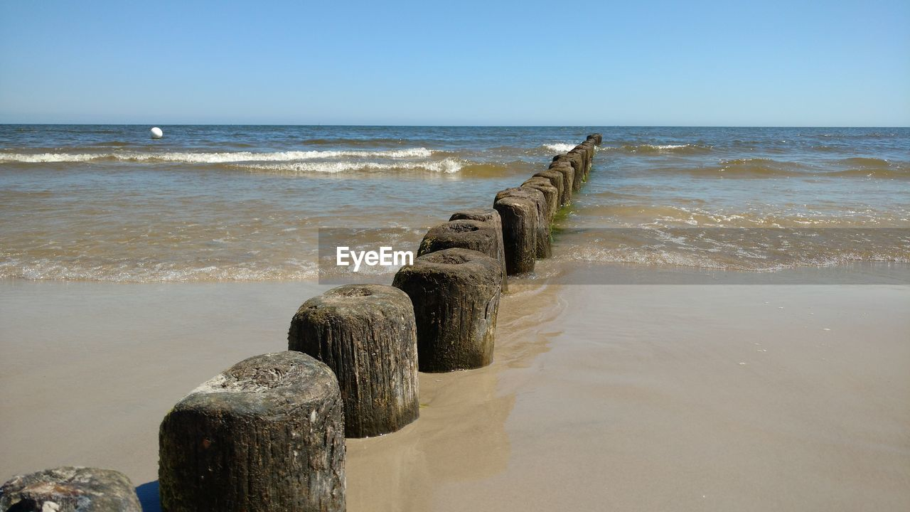 sea, water, sky, beach, horizon, land, horizon over water, scenics - nature, beauty in nature, tranquil scene, nature, tranquility, wave, clear sky, no people, motion, day, sunlight, wood - material, outdoors, post, wooden post, groyne