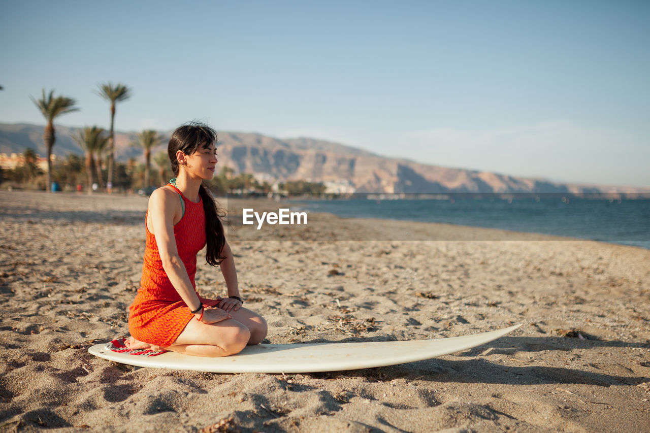 Woman sitting on surfboard at beach