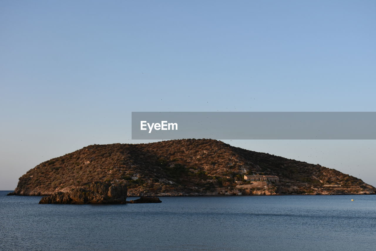 sky, water, clear sky, sea, beauty in nature, copy space, scenics - nature, waterfront, nature, tranquil scene, tranquility, no people, rock, land, mountain, day, outdoors, blue, idyllic