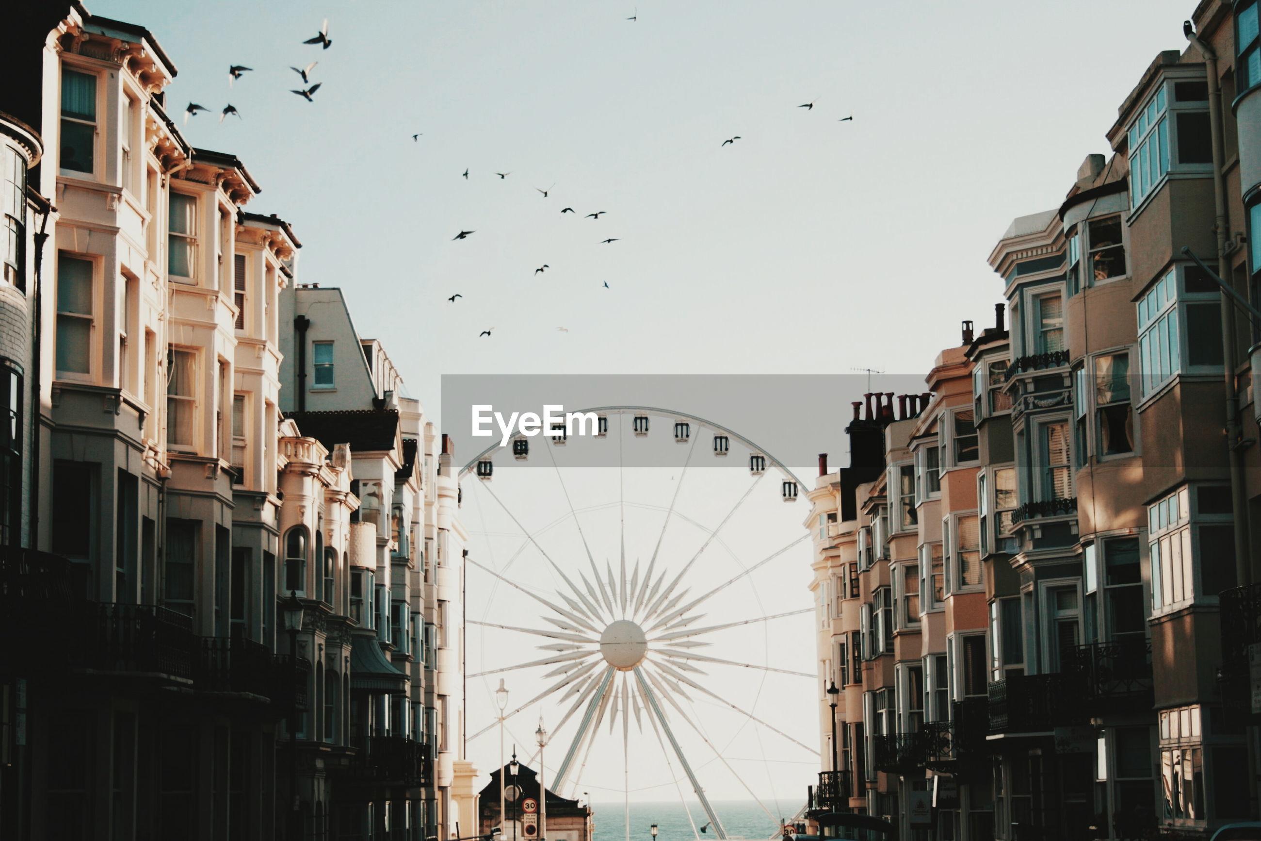 Ferris wheel amidst building against clear sky