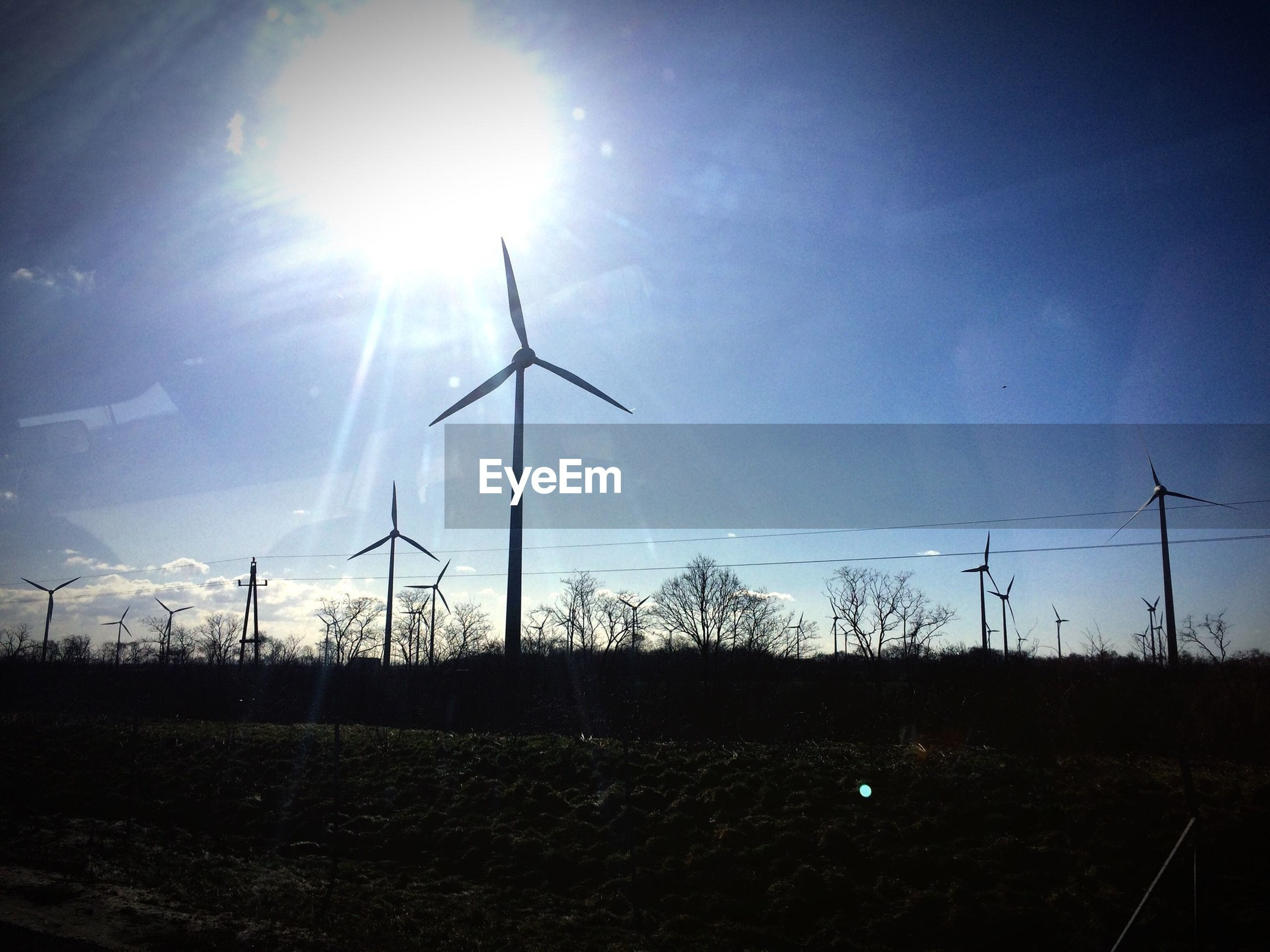 Wind turbines on landscape against blue sky