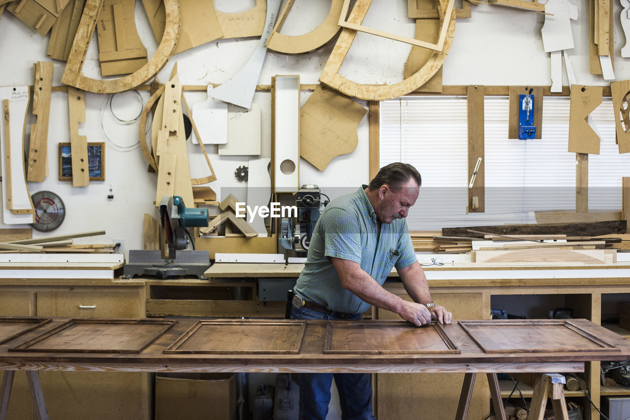 occupation, business, small business, workshop, one person, wood - material, indoors, working, adult, skill, table, men, real people, art and craft, craft, business person, males, casual clothing, expertise, entrepreneur, workbench