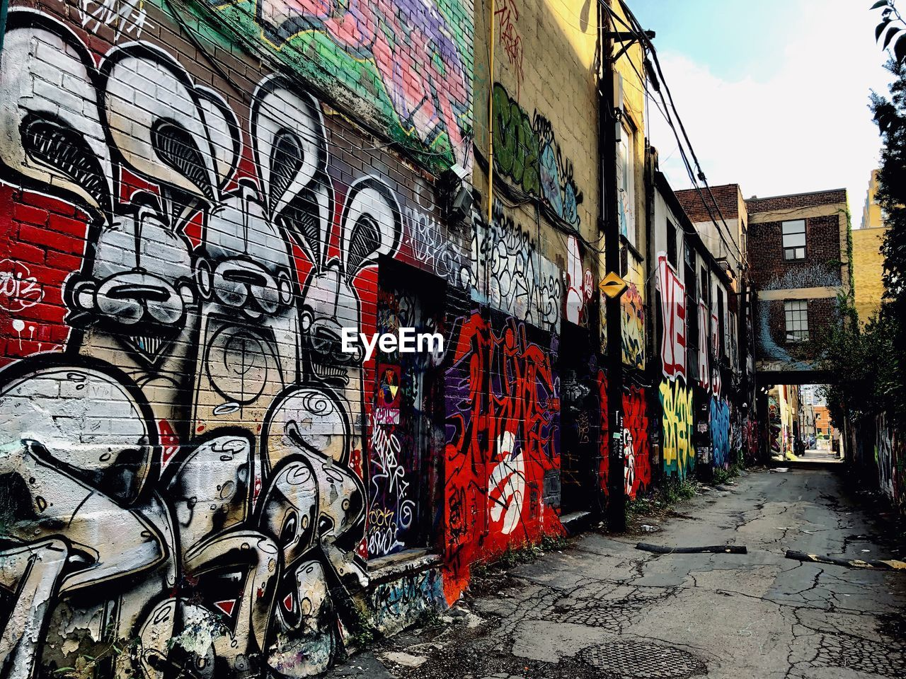 architecture, graffiti, built structure, building exterior, art and craft, creativity, building, city, wall - building feature, multi colored, day, street art, no people, street, outdoors, craft, communication, messy, text, mural, alley