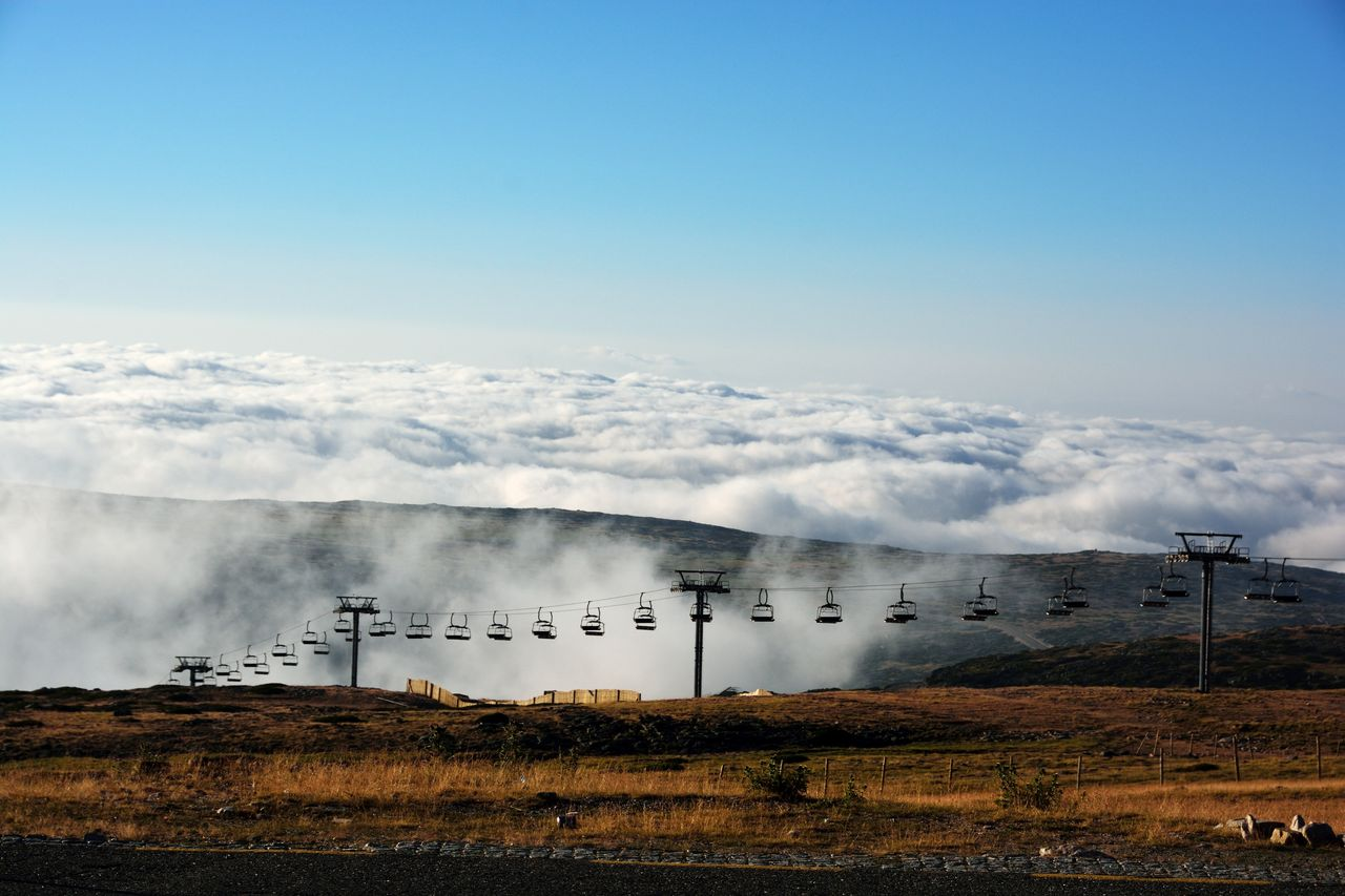 Ski Lifts By Mountains Against Sky During Foggy Weather