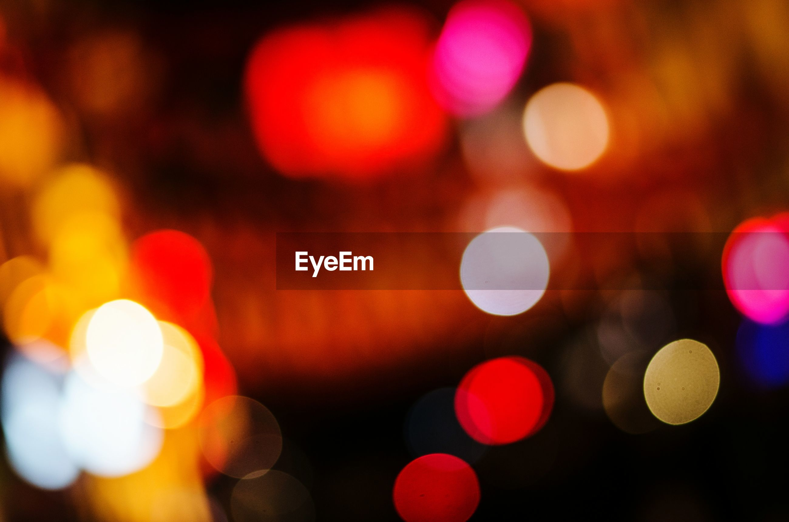 Defocused image of illuminated colorful lights at night