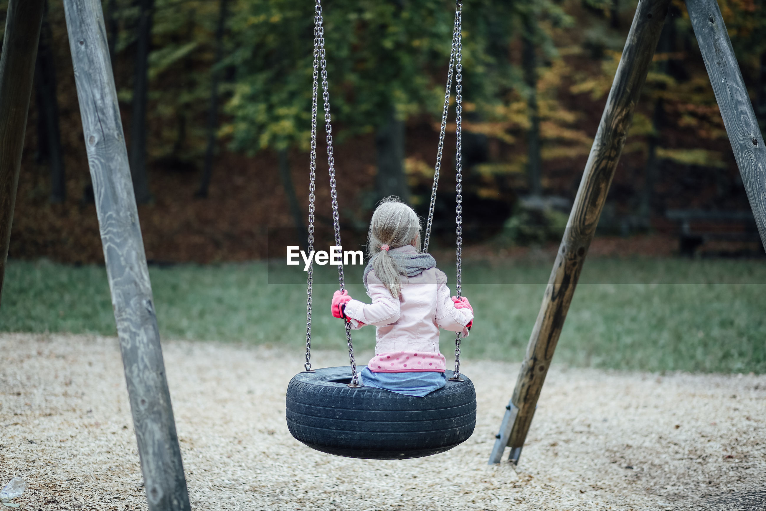 Rear view of girl sitting on tire swing at playground