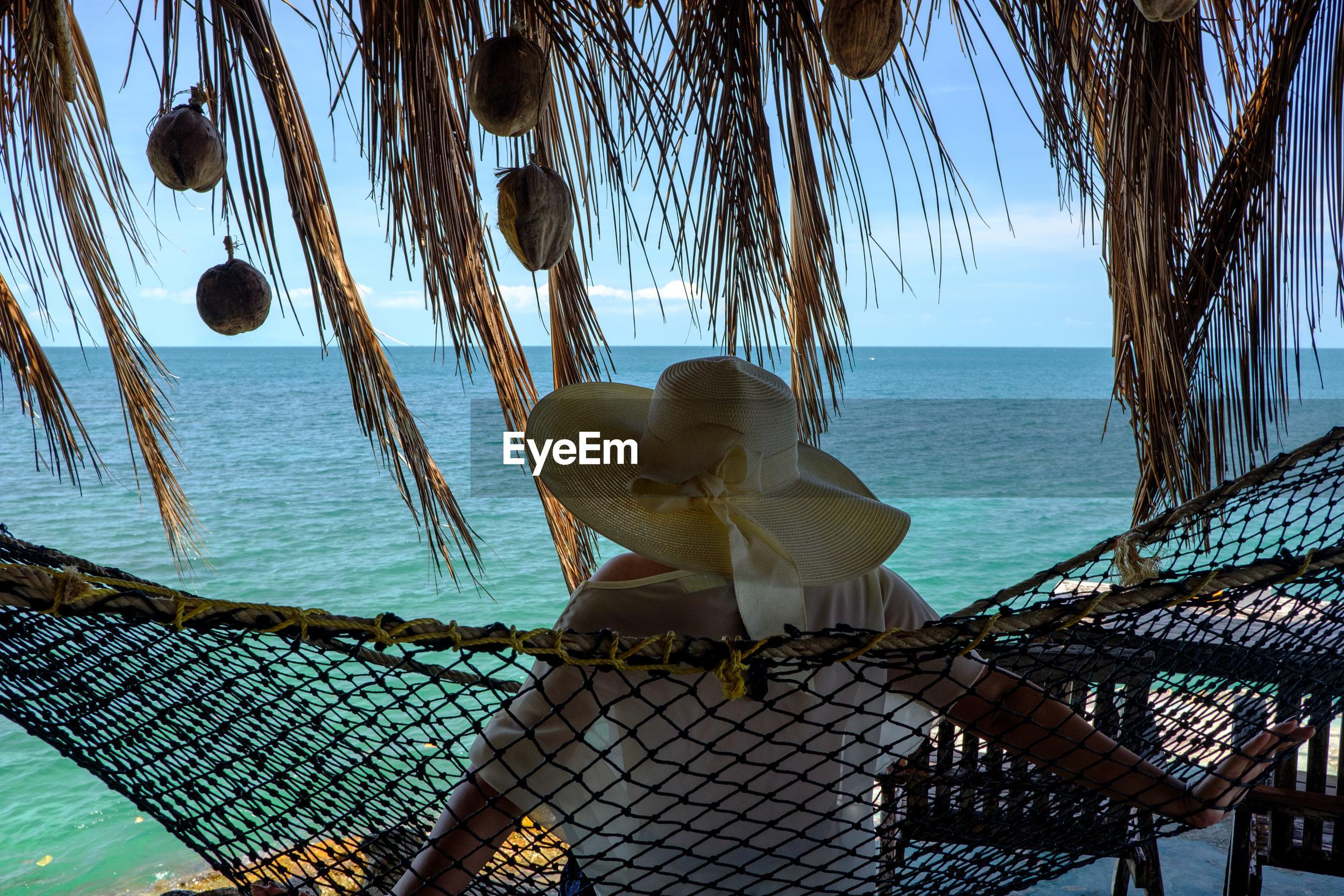 Woman sitting in hammock at beach