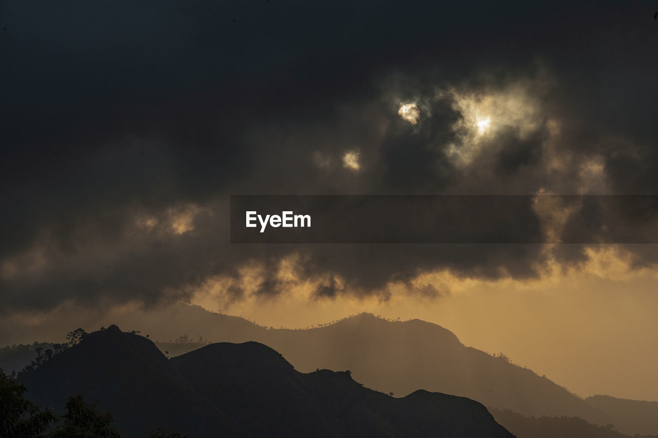 sky, cloud - sky, beauty in nature, mountain, scenics - nature, tranquility, tranquil scene, sunset, silhouette, nature, no people, low angle view, outdoors, idyllic, mountain range, non-urban scene, dusk, majestic, overcast, mountain peak
