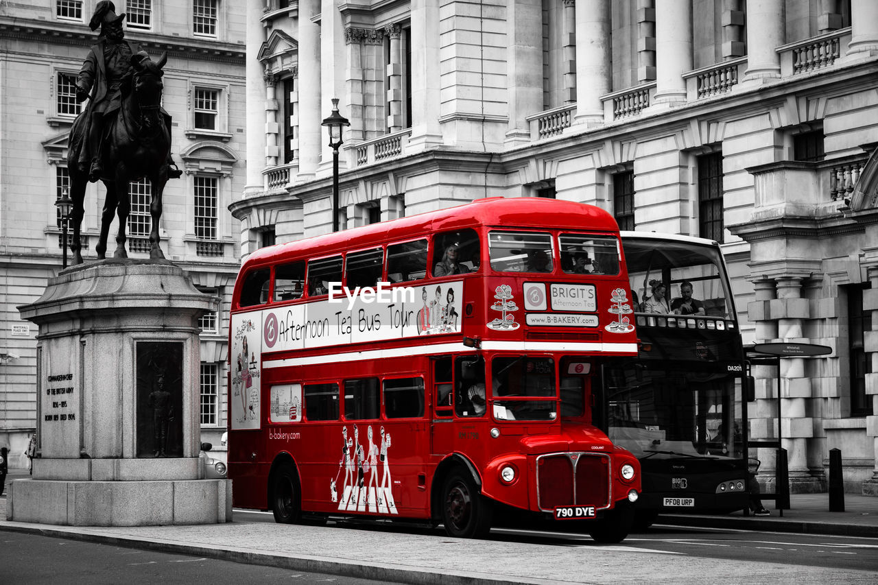 building exterior, architecture, built structure, city, red, day, mode of transportation, transportation, street, text, land vehicle, communication, outdoors, road, western script, double-decker bus, building, public transportation, incidental people, people