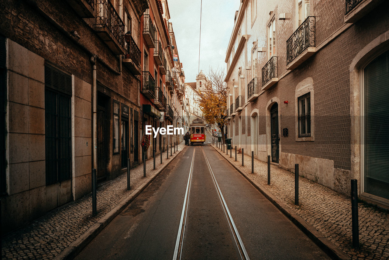 architecture, built structure, building exterior, the way forward, transportation, direction, building, city, street, diminishing perspective, road, mode of transportation, sign, no people, day, symbol, residential district, road marking, marking, vanishing point, outdoors, long, alley