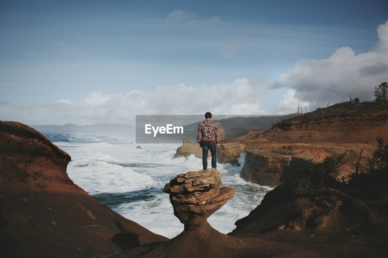 Hiker standing on rock while looking at sea amidst rock formation against sky