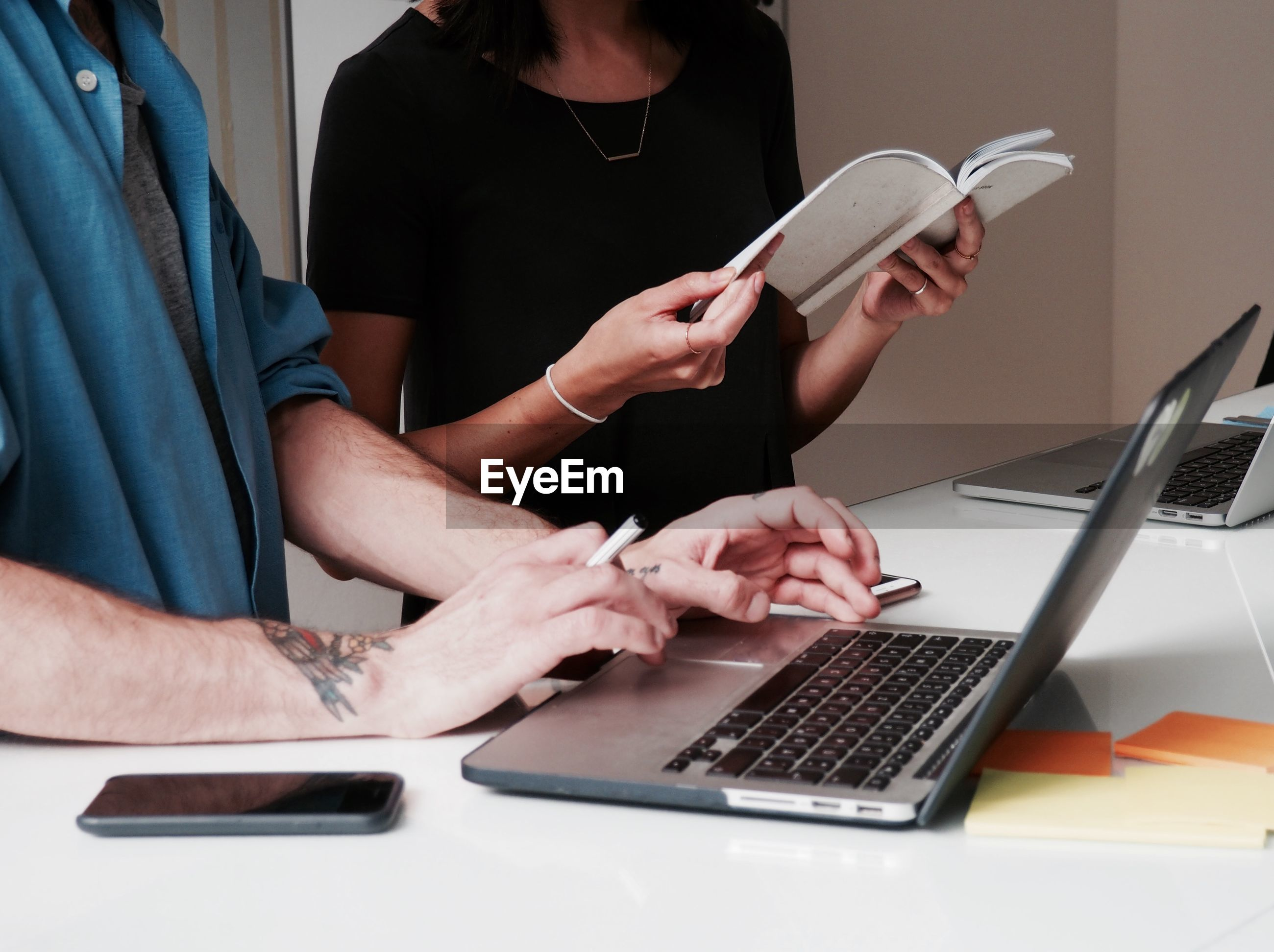 Midsection of man with woman using laptop at desk in office