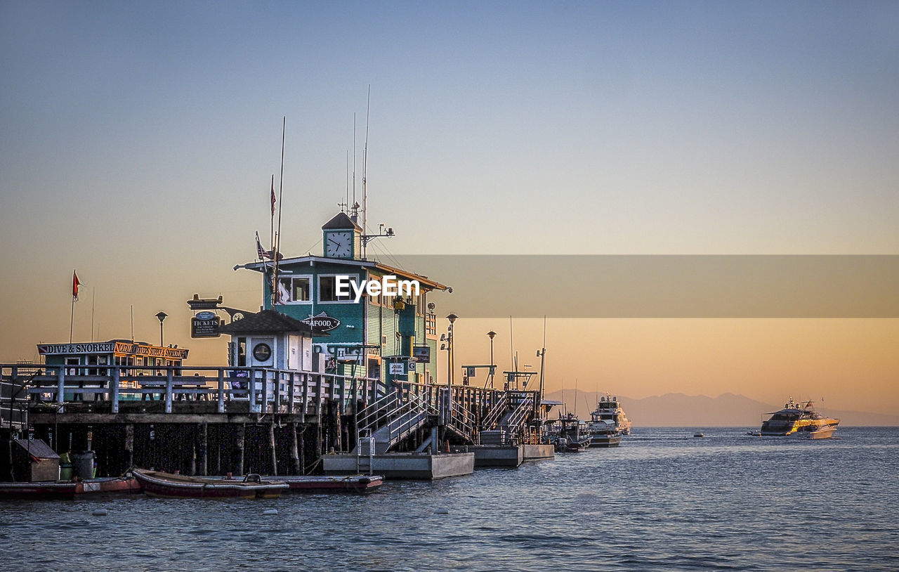 nautical vessel, water, clear sky, sea, waterfront, transportation, sunset, mode of transport, built structure, architecture, sky, outdoors, scenics, no people, nature, building exterior, harbor, day, beauty in nature, horizon over water