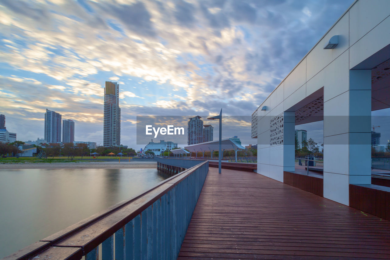 architecture, built structure, sky, cloud - sky, building exterior, water, city, building, nature, railing, office building exterior, skyscraper, travel destinations, sunset, connection, modern, no people, office, outdoors, financial district