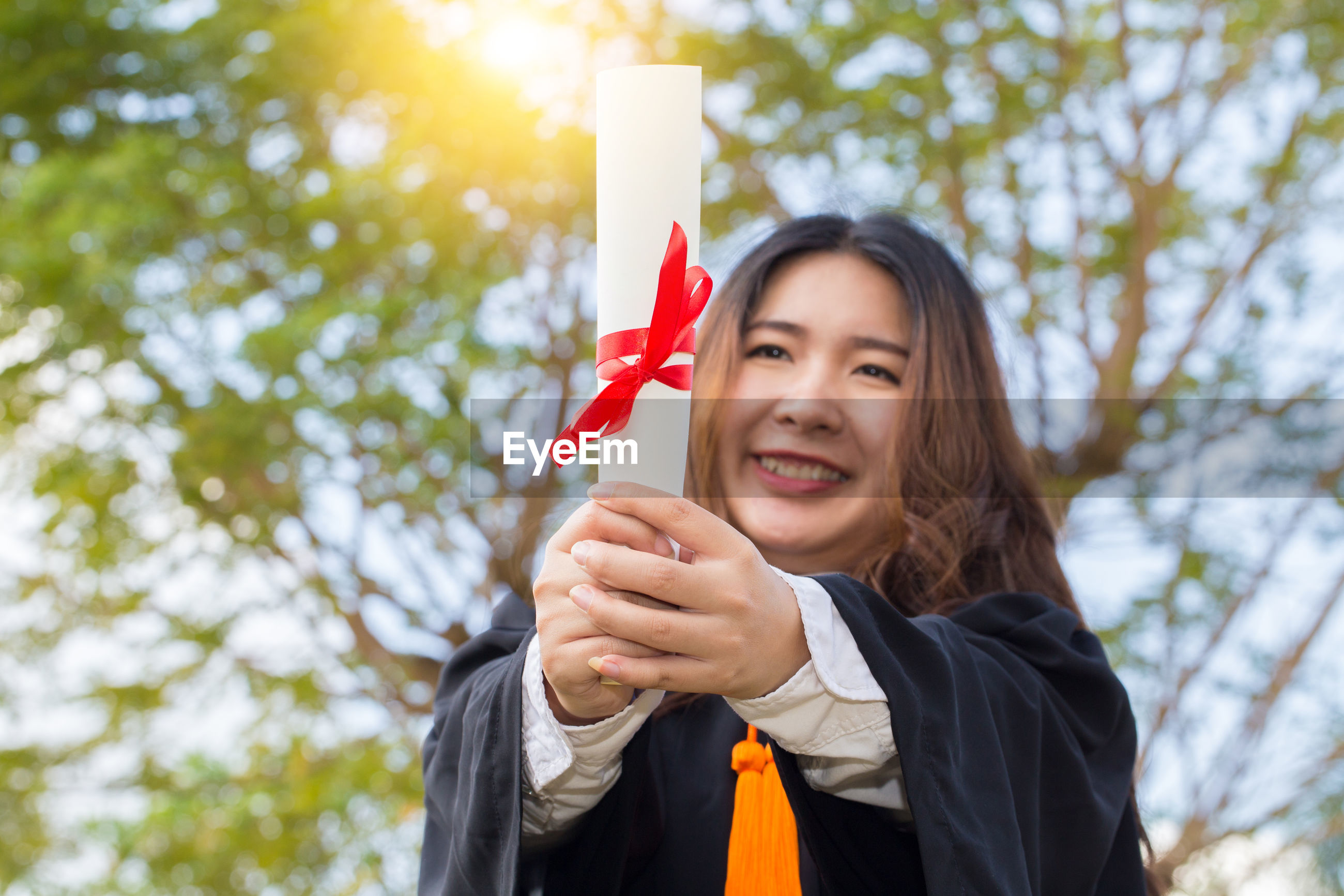 Smiling young woman wearing graduation gown while holding diploma against trees
