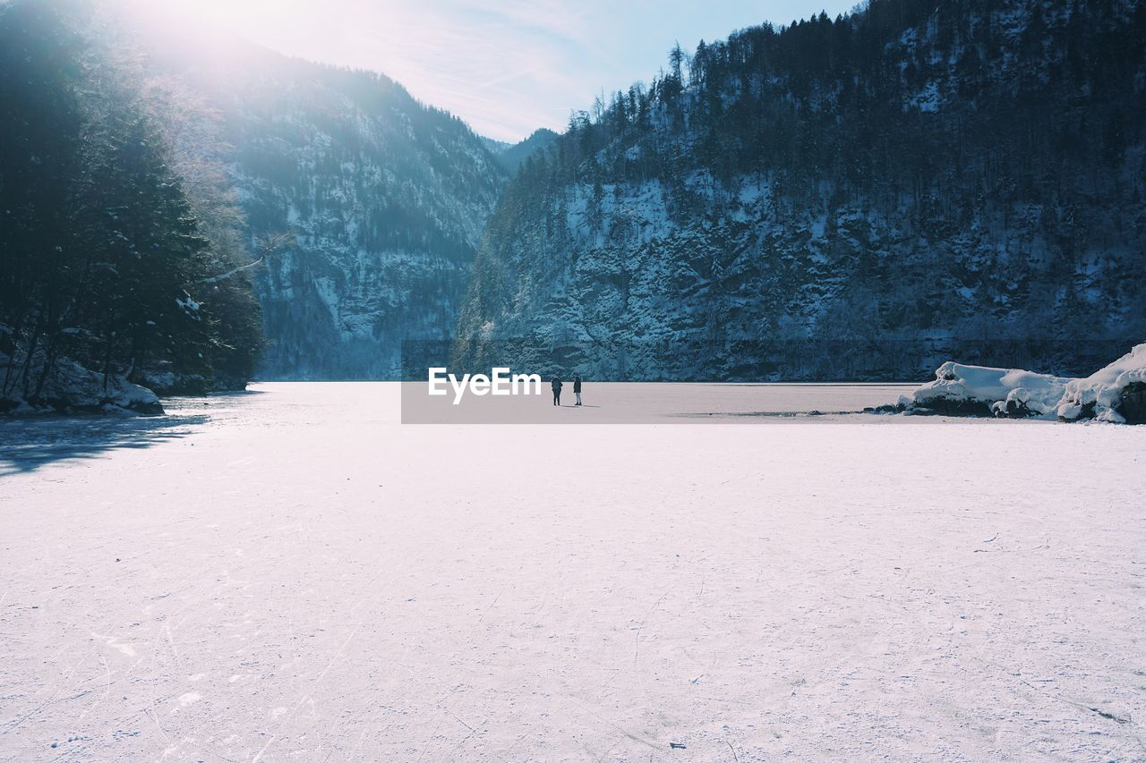 Man Walking On Snow Covered Landscape