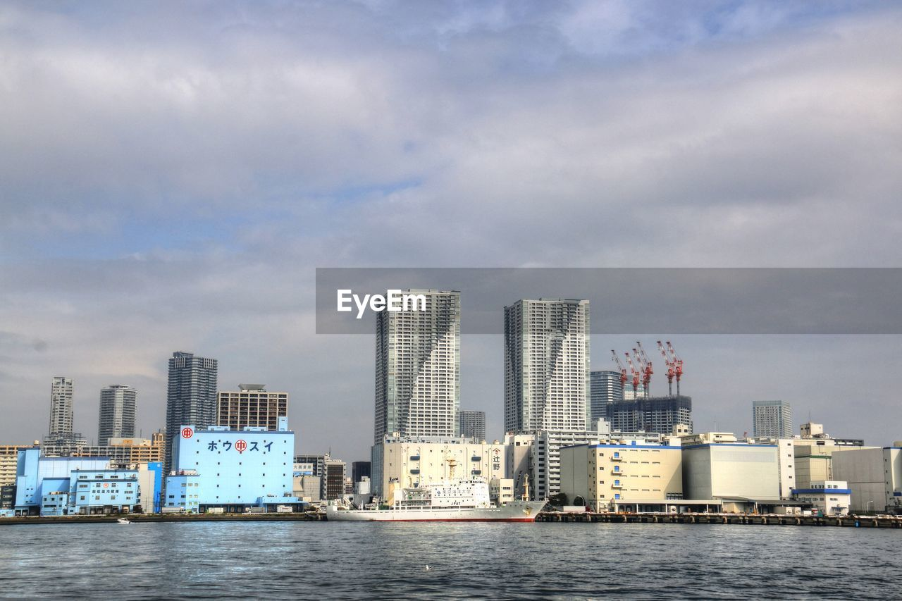 architecture, building exterior, built structure, skyscraper, waterfront, sky, modern, city, cloud - sky, no people, sea, water, day, cityscape, outdoors, urban skyline, nautical vessel, nature