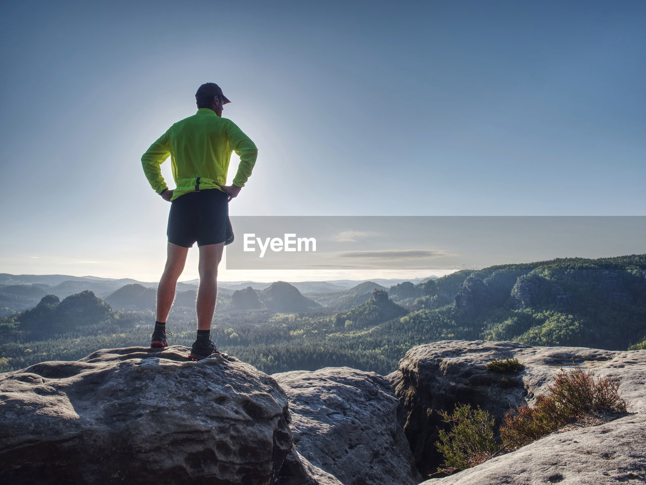 Runner workout outdoor in rocks during trail marathon on mountain path. sunny lens flares
