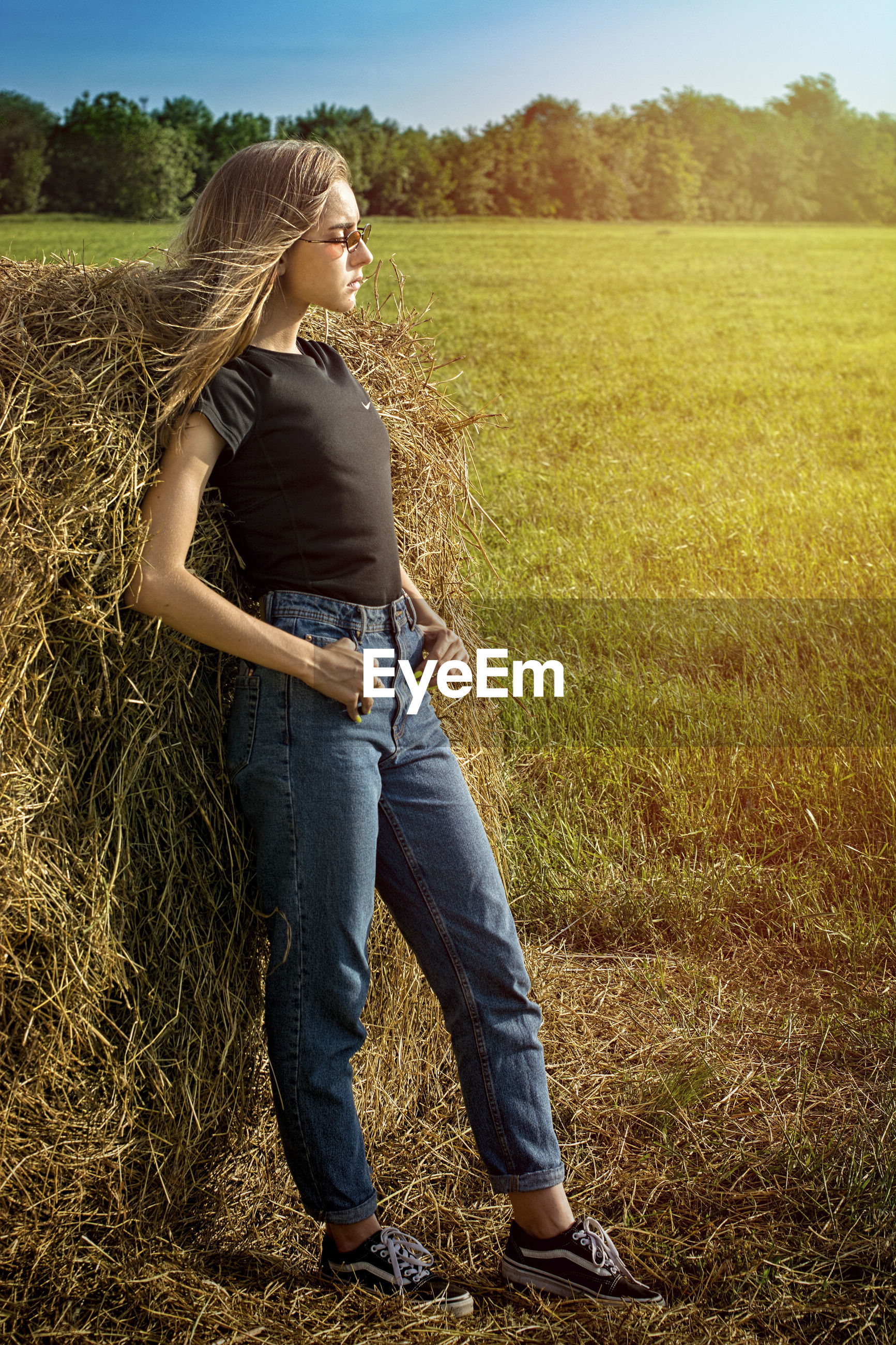 Side view of young woman standing on grassy field by hay bale