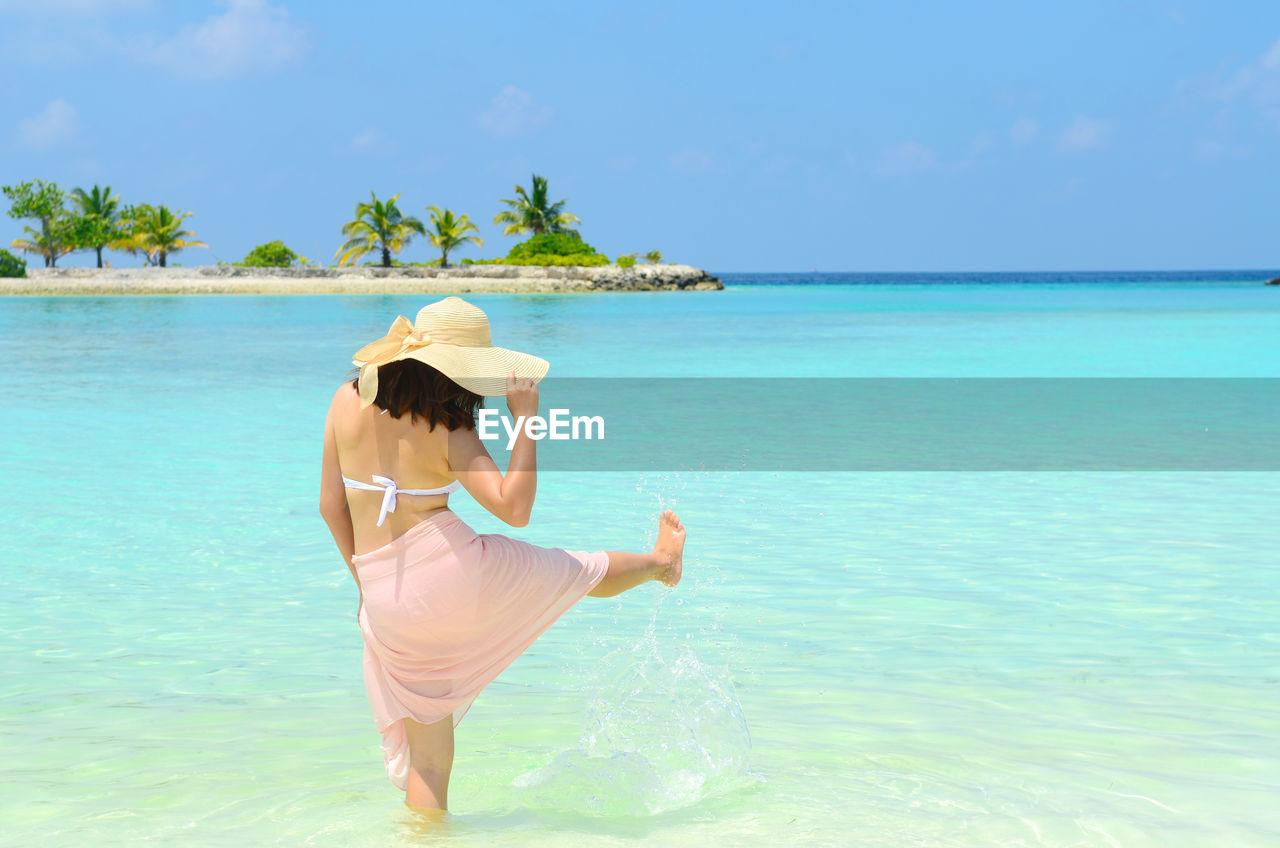 Rear view of woman wearing hat splashing water at sea