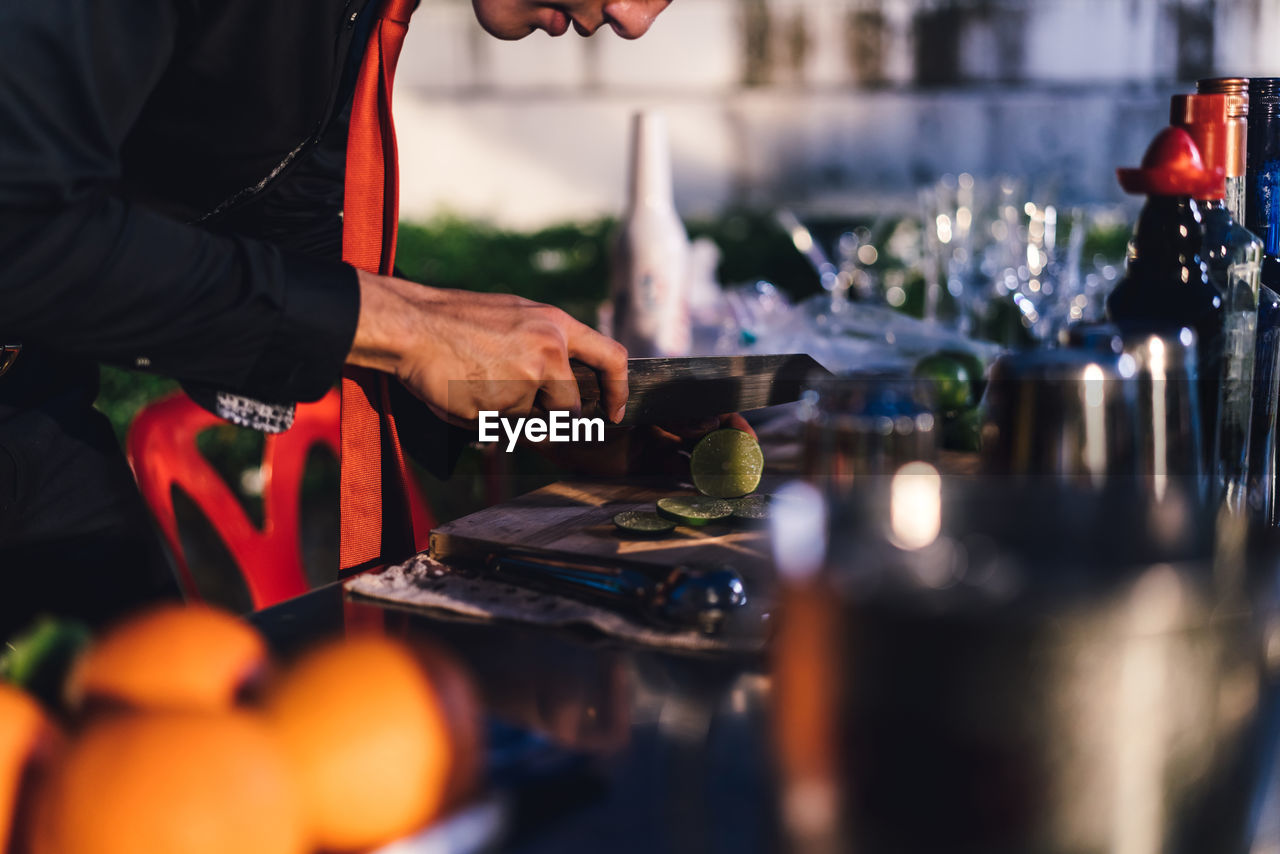 Young bartender working in party at night