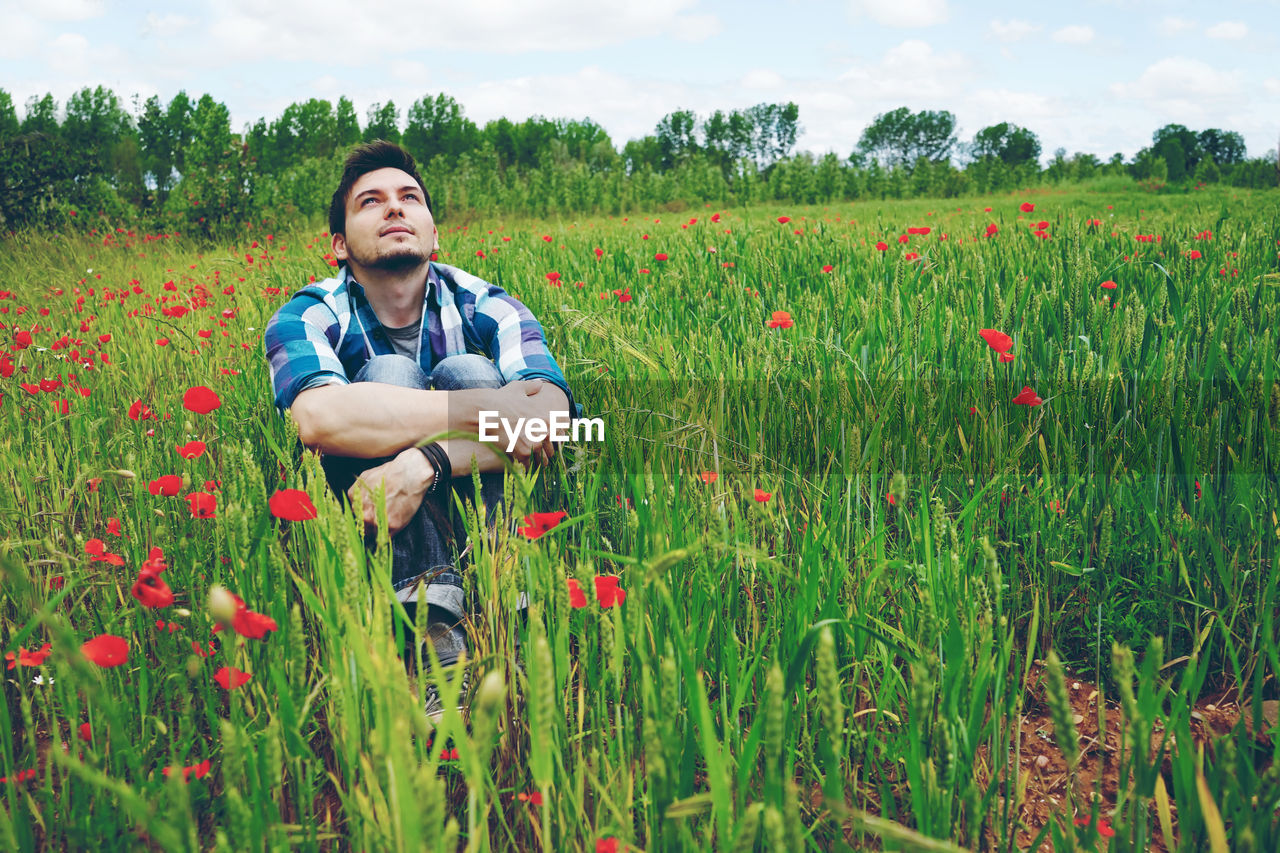 Thoughtful Mid Adult Man Hugging Knees While Sitting Amidst Plants On Field
