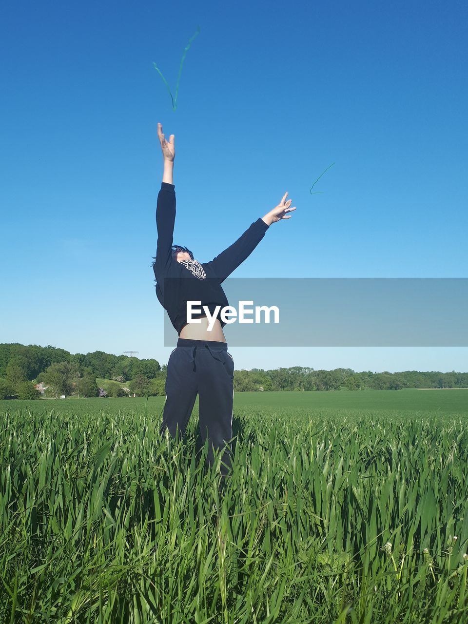 Boy With Arms Raised Standing On Field Against Clear Sky