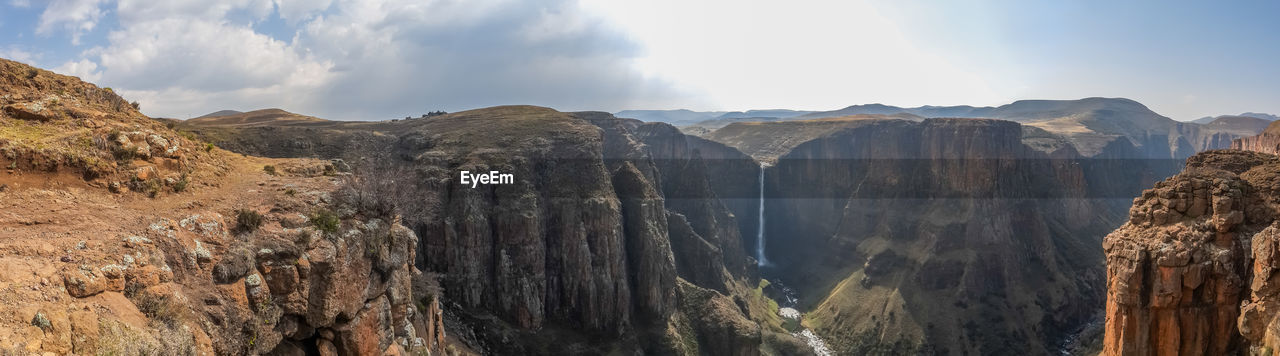 Panoramic view of landscape with canyon and maletsunyane waterfall against dramatic sky, semonkong, lesotho, africa