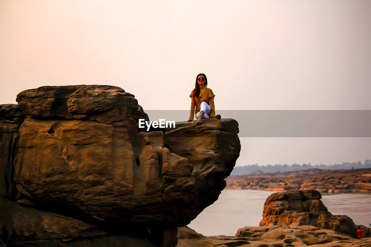 Woman Sitting On Rock At Beach Against Clear Sky