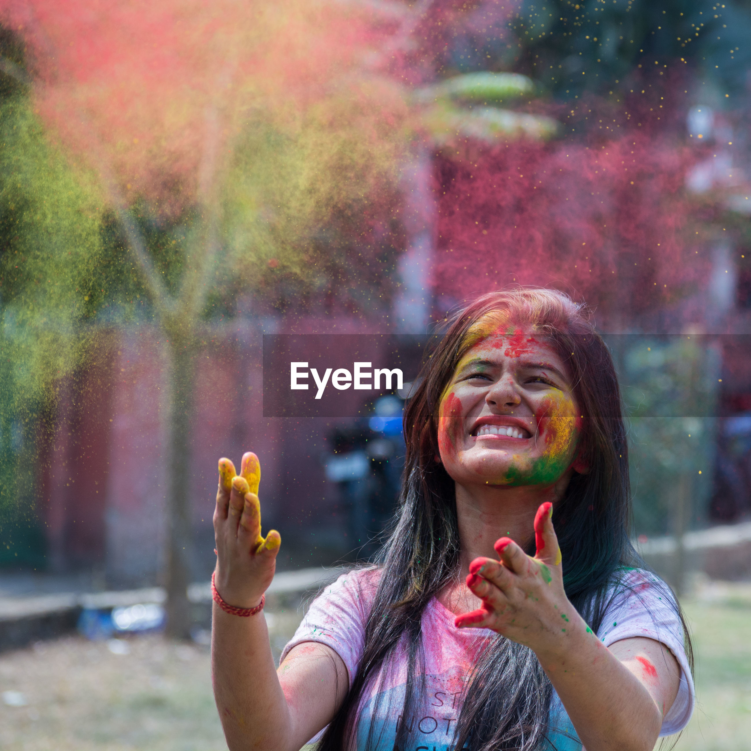Close-up of smiling young woman playing holi