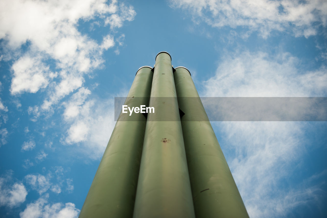 low angle view, sky, cloud - sky, day, no people, nature, outdoors, sunlight, metal, blue, tall - high, green color, architecture, built structure, building exterior, sunny, technology, pipe - tube, directly below, industry