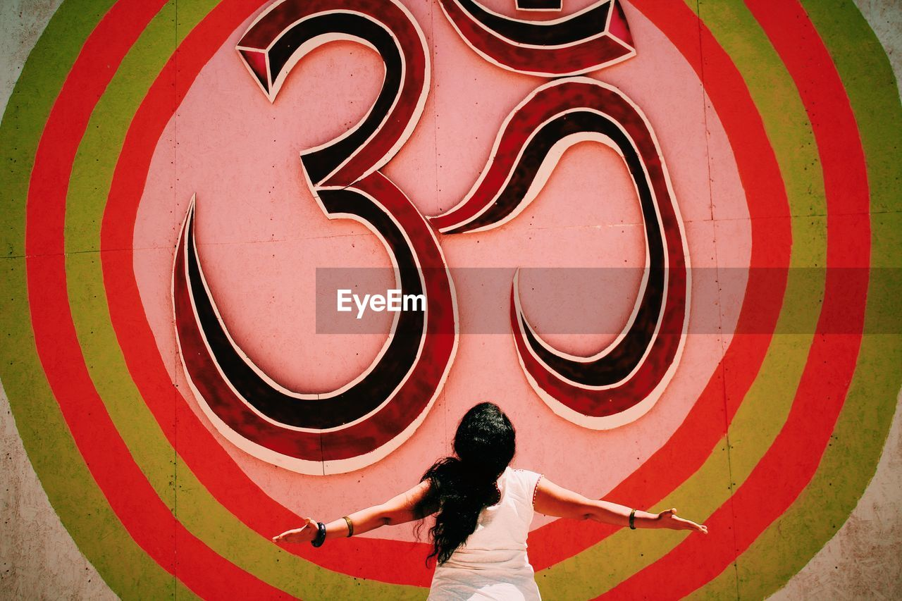 Rear view of woman with arms outstretched standing in front of Om symbol on wall
