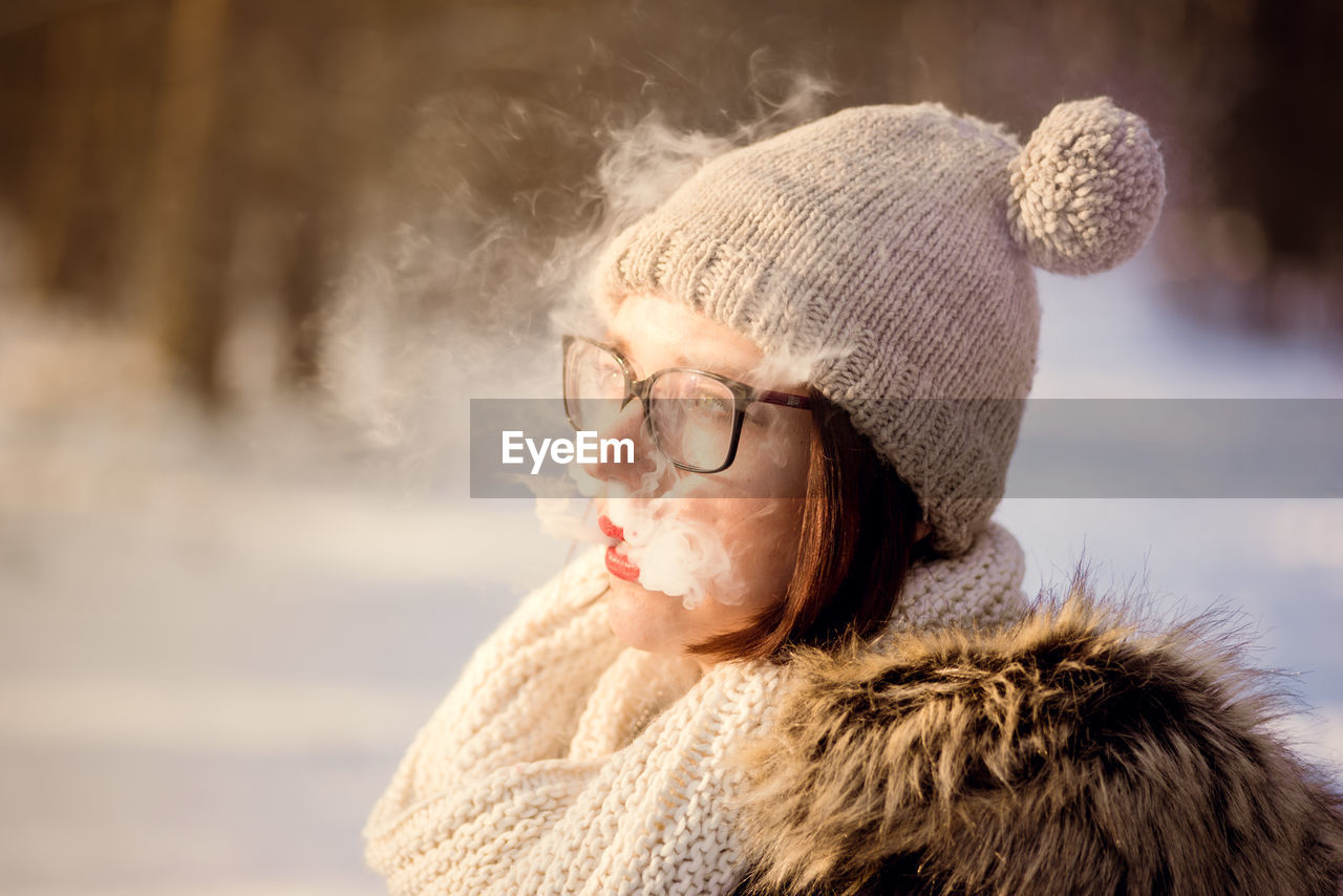 Close-Up Of Woman Wearing Warm Clothing While Smoking During Winter
