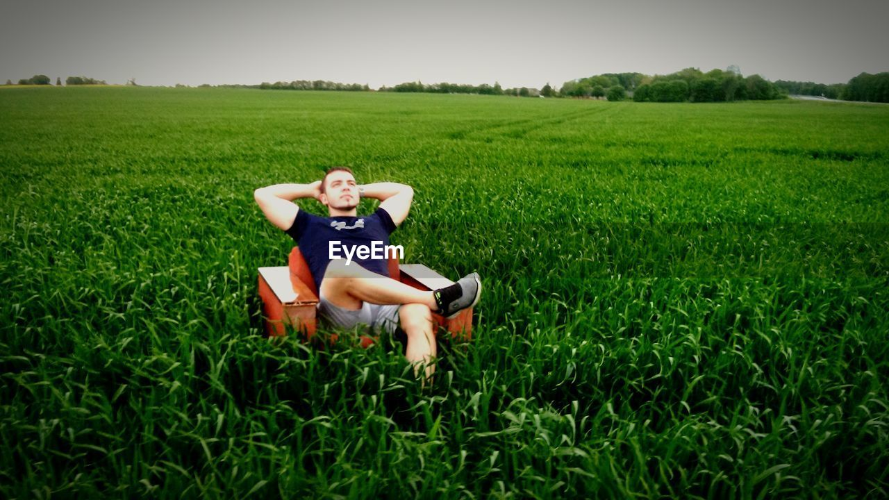 Man Sitting In Sofa In Field