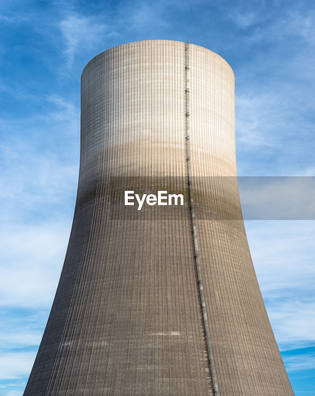 A huge chimney of a nuclear power plant close up on a background of blue sky with clouds.