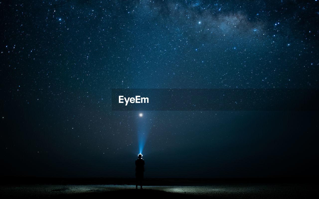 Rear View Of Man Flashing Light In Sky At Night